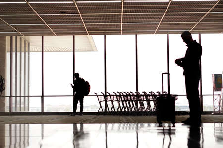 people silhouettes walking across terminal at airport photo
