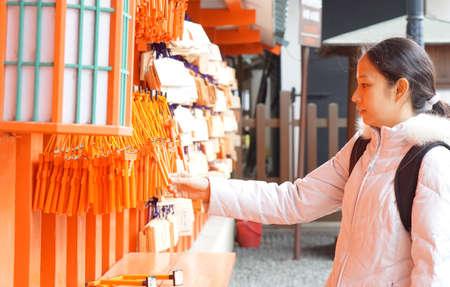 wishing: girl with ema, wishing board in Japanese shrine Stock Photo