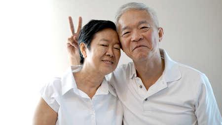 Happy Asian senior couple on white background love and hug