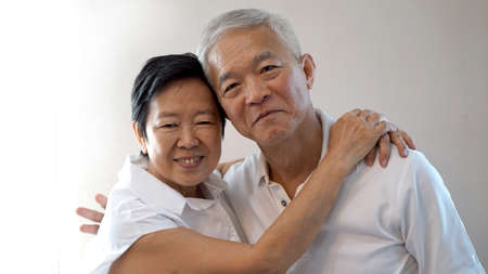 Happy Asian senior couple on white background love and hug