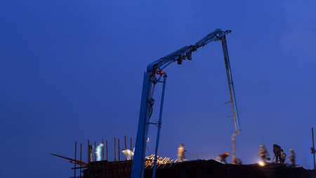 concrete pump: concrete pump working at night with blue sky and sillhoutte