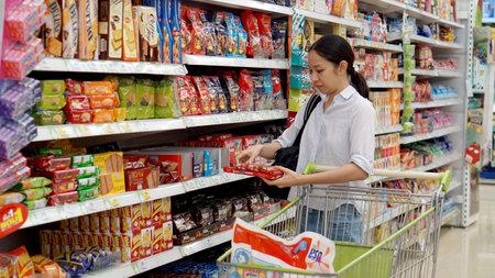 Aziatisch meisje, vrouw winkelen snacks in de supermarkt Redactioneel