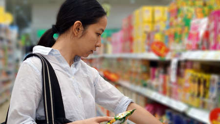 grocery shelves: Asian girl, woman shopping snacks in supermarket
