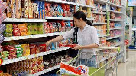 grocery baskets: Asian girl, woman shopping snacks in supermarket
