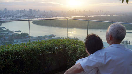 senior looking at sunrise together over city skyline and river Stock Photo