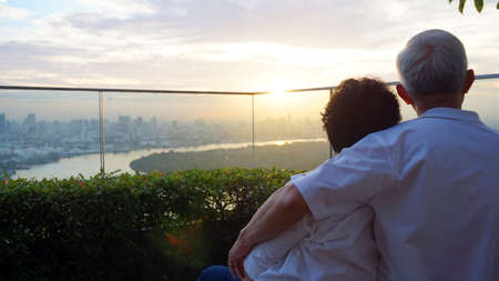 senior looking at sunrise together over city skyline and river Foto de archivo