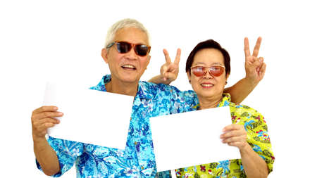 Happy Asian senior couple holding white blank sign ready for holiday trip Stock Photo