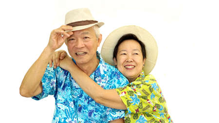 Happy Asian senior couple hugging happily wearing hat ready for holiday trip Stock Photo
