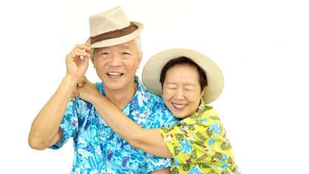 Happy Asian senior couple hugging wearing hat ready for holiday trip Reklamní fotografie
