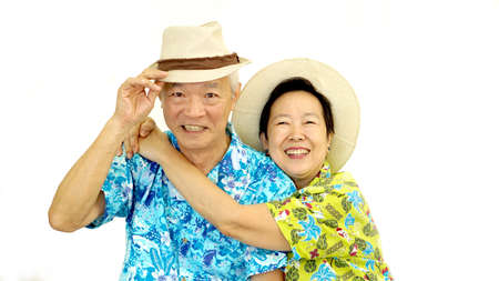 Happy Asian senior couple hugging happily wearing hat ready for holiday trip Banco de Imagens