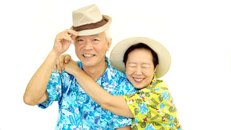 Happy Asian senior couple hugging happily wearing hat ready for holiday trip Reklamní fotografie