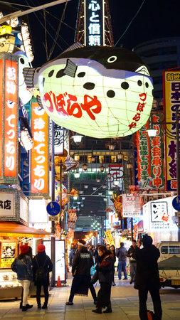 neon fish: Osaka, Japan - March 2015: shinsekai, tsutenkaku restaurant street area with landmark fish latern neon sign Editorial