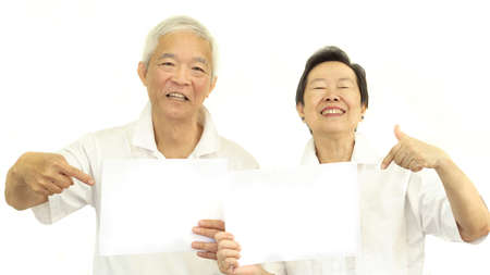 man holding card: Happy Asian senior couple holding white blank sign ready for promotion advertising banner Stock Photo