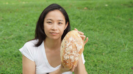 carbohydrates: Asian woman mature adult eating bread carbohydrates