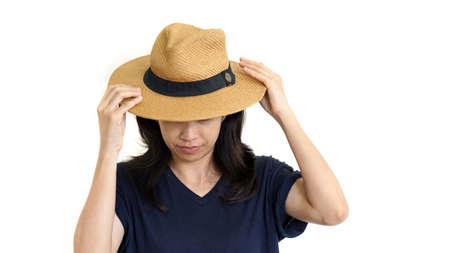 south east asian: Casual South East Asian girl wearing hat hiding face, upset