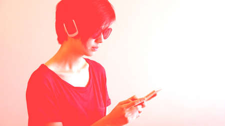 Asian cool hipster girl wearing sunglasses and headphone, urban lifestyle concept with abstract red light grading