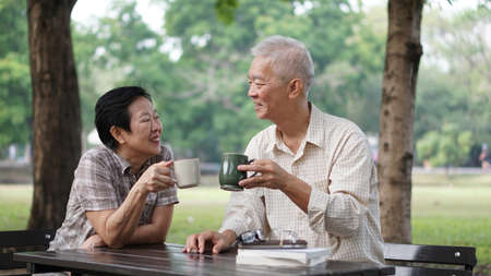 Asian senior couple reading books, learning investment and drinking coffee in the park