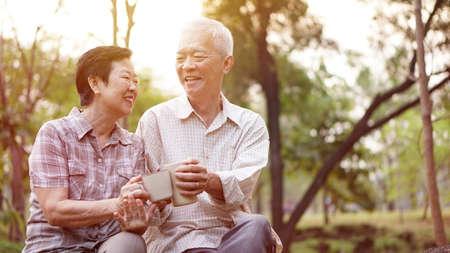 아침 공원에서 함께 커피를 마시는 건강한 아시아 수석 부부는 함께
