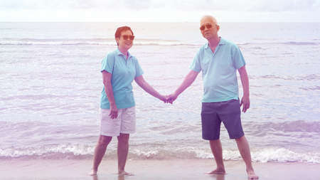 Asian senior couple walking together on the beach by the sea Stock Photo
