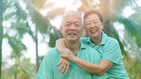 Asian senior couple relaxing in the park laughing in sunshine Banco de Imagens