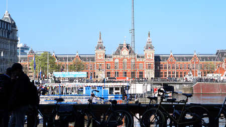 Amsterdam, Netherlands - 3 April 2017: Amsterdam main station from across the canal with people and bike silhouette Editorial