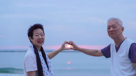 Asian senior couple together at sunrise beach. New year, new chapter concept Stock Photo - 81193322