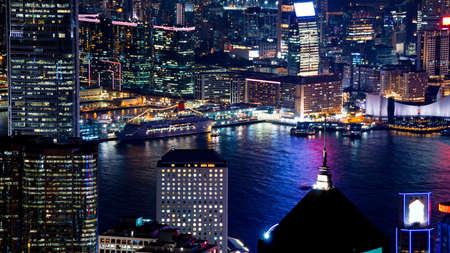Hong Kong Victoria harbour and its iconic red ancient junk sail zoom shot from the Peak at night Sajtókép