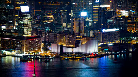 Hong Kong Victoria harbour and its iconic red ancient junk sail zoom shot from the Peak at night Stock Photo