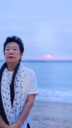Asian senior standing alone and thinking at mornign beach sunrise