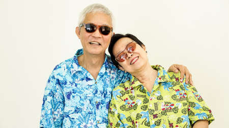 Happy Asain senior couple ready to travel for holiday on white background