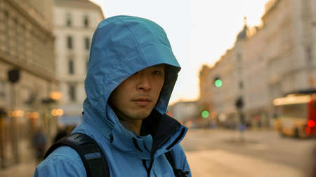 Asian man with outdoor jacket with sunset, European architecture background