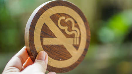 Hand holding wooden no smoking sign