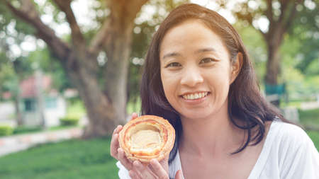 Asian woman holding and eating fresh baked bread bakery in green background park