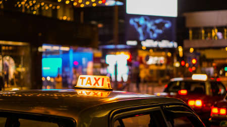 Taxi sign at night blur view in pub and bar nightlife area. Stock Photo