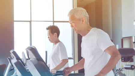 Old healthy Asian senior couple exercise together in gym running treadmill Stock Photo