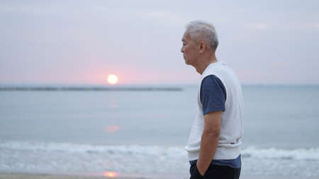 Asian senior man standing at sunrise ocean thinking about life