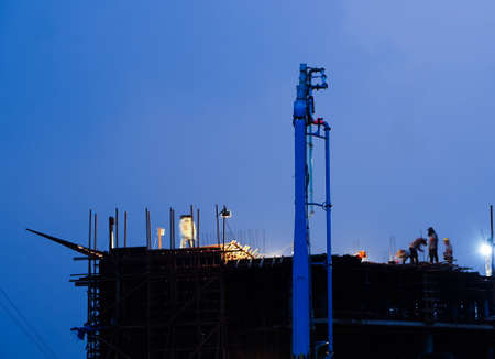Construction crane truck working on structure at night with light
