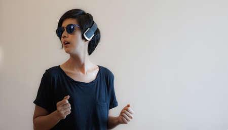 Asian woman hipster lifestyle using headphones and wearing eyeglasses Reklamní fotografie