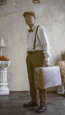 Retro vintage fashion Asian senior man with flat cap and suspender carry luggage for travel lifestyle Stock Photo