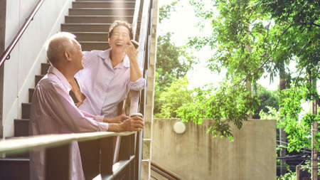 Asian elderly professional couple talking outdoor morning in modern building Stock Photo