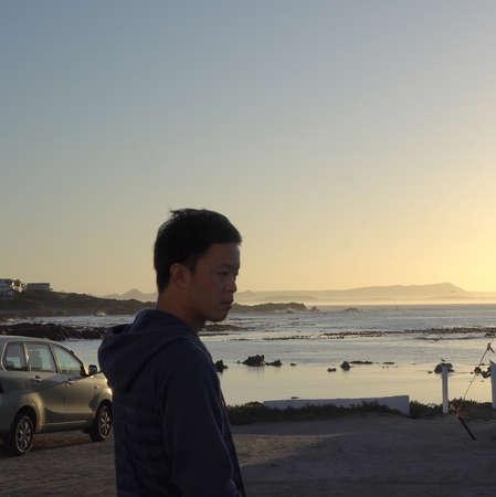 Asian man at beach sea early morning golden sunrise abstract beautiful life