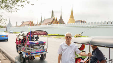 Bangkok, Thailand - 18 Mar 2016 : Senior Asian man travel in Bangkok landmark with tuk tuk