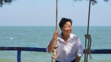 Asian senior woman alone at sea sunrise Stockfoto