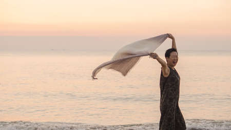 Happy Asian senior woman tun at beach with scarf and copy space Stockfoto