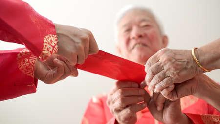 Hand, die roten Umschlag für chinesisches neues Jahr gibt