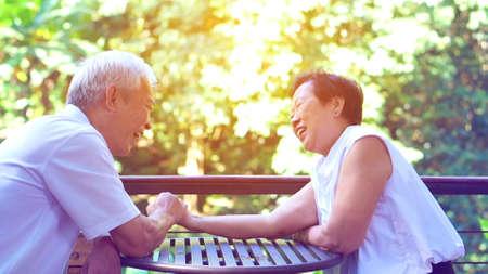 Asiatisches älteres altes Ehepaar, das im Spiel des Liebesgeheimnisses der dauerhaften Liebe Kompromisse eingeht