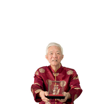 Asian senior man give gold pig sculpture for Chinese new year Stock Photo