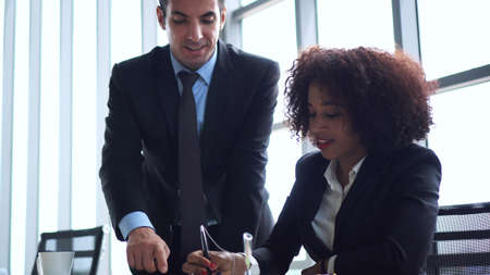 Hispanic and African colleague discuss work together for better result