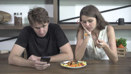 Fighting Caucasian couple smart phone addict problem while eating dinner at home