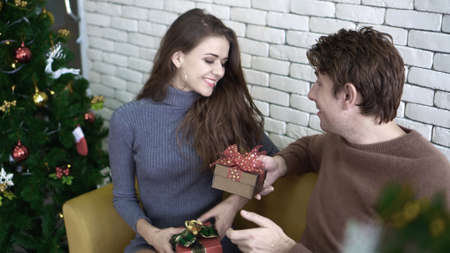 Happy lovely Caucasian couple exchange gifts on Christmas day